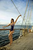 Young woman in stylish swimsuit posing pretty on the sail boat. stock photography
