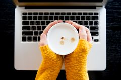 Young woman in stylish yellow sweater holding cup in hands. stock photos