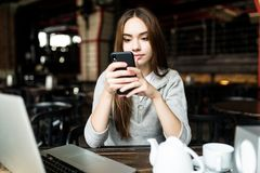 Young woman or successful working on smart phone and laptop computer at coffee shop interior. Girl student sitting in university c. Afeteria while using royalty free stock photos