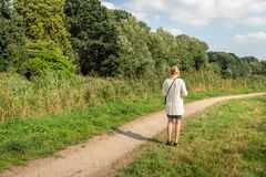 Young woman suddenly stands still during her walk. Young woman with blond hair pinned up and a knitted white colored vest suddenly stops on a walking path to royalty free stock image