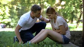 Young woman suffering abdominal ache in park, man offering help, first aid royalty free stock images