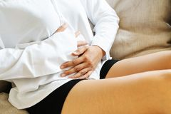 Young woman suffering from abdominal pain while sitting on the sofa and feeling stomachache, symptom of pms stock photo