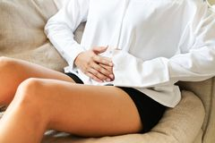 Young woman suffering from abdominal pain while sitting on the sofa and feeling stomachache, symptom of pms stock photography
