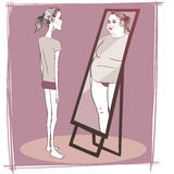 Young woman suffering from anorexia. Looking in the mirror Royalty Free Stock Photography