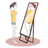 Young woman suffering from anorexia. Looking in the mirror Stock Photography