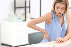 Young woman suffering from back pain. In office Royalty Free Stock Photography