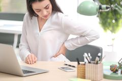 Young woman suffering from back pain. In office Stock Image