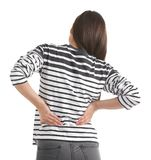 Young woman suffering from back pain. On white background Stock Photos