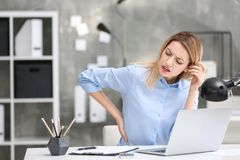 Young woman suffering from back pain. In office Stock Photo