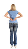 Young woman suffering from backache. Back view of an attractive young woman suffering from backache. All on white background Royalty Free Stock Photography