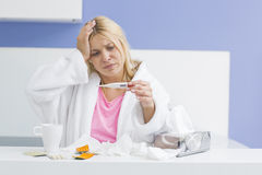 Young woman suffering from cold checking tempereature. Young women suffering from cold checking tempereature Royalty Free Stock Image