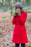 Young woman suffering from a cold or flu blowing her nose. On a white paper handkerchief on a forest wearing a red overcoat, a beanie and gloves during winter Royalty Free Stock Images