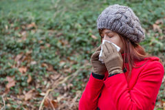 Young woman suffering from a cold or flu blowing her nose. On a white paper handkerchief on a forest wearing a red overcoat, a beanie and gloves during winter Stock Photos