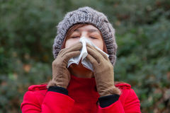 Young woman suffering from a cold or flu blowing her nose Stock Photos