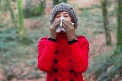 Young woman suffering from cold or flu blowing nose or sneezing on white paper handkerchief royalty free stock image