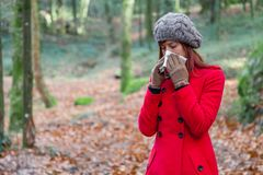 Young woman suffering from cold or flu blowing nose or sneezing on white paper handkerchief. In forest wearing a red long coat or overcoat, a beanie and gloves Stock Photo