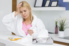 Young woman suffering from cold in kitchen Stock Image