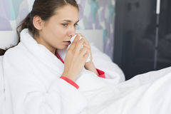 Young woman suffering from cold using tissue paper in bedroom Royalty Free Stock Photo