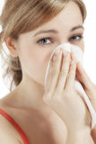 Young woman suffering on hay fever. Young blonde woman suffering on hay fever sneezing with a paper tissue Royalty Free Stock Photography