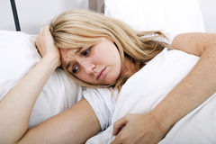 Young woman suffering from headache in bed Stock Photo