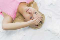 Young woman suffering from headache while lying on bed Stock Photography