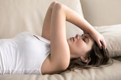 Young woman suffering of headache or migraine. Woman lying on sofa having headache. Stressed girl suffering of fatigue, migraine, trying to cope with nervous Stock Photography