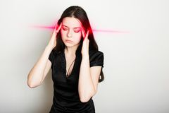 Young woman is suffering from a headache. Portrait of a girl clutching her head. Migraines and blood pressure problems royalty free stock photo