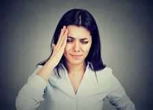 Young woman suffering from headache touching her head with hand Stock Image