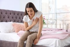 Young woman suffering from heart attack on bed. At home stock images