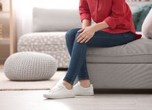Young woman suffering from knee pain. At home stock image