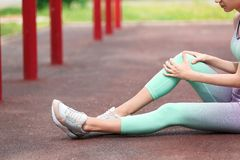 Young woman suffering from knee pain on sports ground. Closeup stock photos