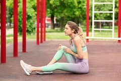 Young woman suffering from knee pain. On sports ground royalty free stock images