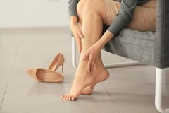 Young woman suffering from leg pain because of uncomfortable shoes while sitting on sofa. At home stock photography