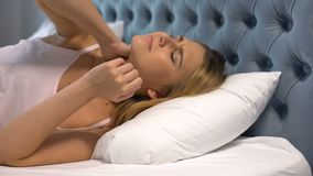 Young woman suffering neck pain lying on uncomfortable pillow, hard mattress