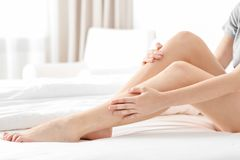 Young woman suffering from pain in leg. At home stock images