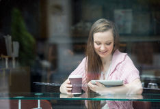 Young pretty woman drinking coffee in cafe Royalty Free Stock Image