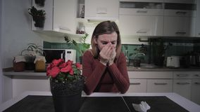 Young woman suffering from a respiratory illness allergic to flowering house plants, sneezes and wipes with handkerchief. Young woman suffering from a stock video