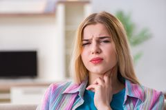 The young woman suffering from sore throat pain stock image
