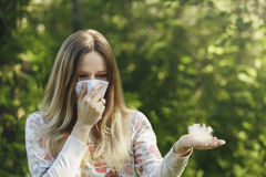 Young woman suffering spring pollen allergy. Sneezing into a white handkerchief, holding a sprig with fuzz royalty free stock photo