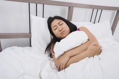 Young woman suffering from stomach ache lying in bed stock photography