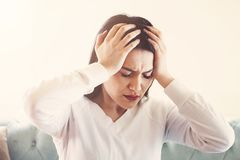 Young woman suffering from strong headache or migraine sitting at home, millennial guy feeling intoxication and pain touching achi. Ng head, morning after royalty free stock images