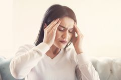 Young woman suffering from strong headache or migraine sitting at home, millennial guy feeling intoxication and pain touching achi. Ng head, morning after stock photography