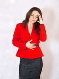 A young woman suffers from a headache. A young woman between 30 and 40 years old dressed in a classical red jacket with a headache and stomachache royalty free stock photo