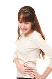 Young woman suffers from lumbago. Studio shot of young woman on white background Stock Images
