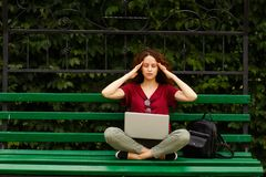 A curly young woman with closed eyes, working on a laptop, seated on a green bench in park touche her temples. stock photo