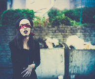 Young woman suffocating herself in garbage environment. Artistic image of young blindfolded woman suffocating herself in garbage environment Stock Images