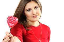 The young woman with sugar candy heart on a stick Royalty Free Stock Photography
