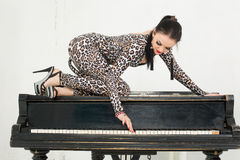 Young woman in a suit with an animal coloring sits on the piano Stock Photo