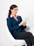 Young woman in a suit and glasses reading a book Royalty Free Stock Images