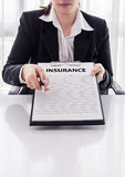 Young woman in suit in his office showing an insurance policy an Royalty Free Stock Photos